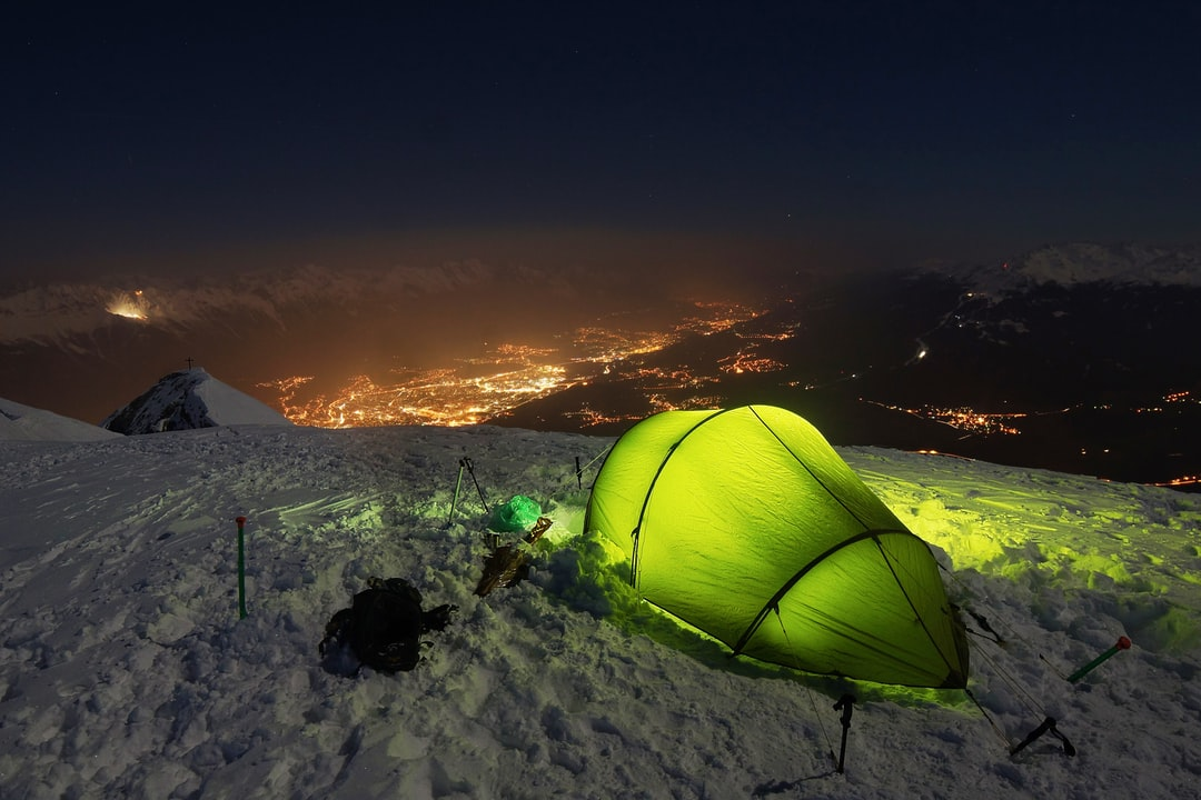 A close up of a green tent on top of a mountain